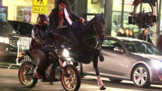 Keanu Reeves follows a motorcycle on a horse
